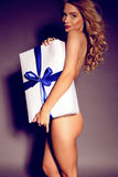Sexy charming naked woman  holding a big present Royalty Free Stock Images