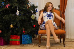 Sexy charming woman sitting on chair with legs crossed Royalty Free Stock Images