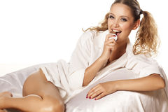 Sexy chocolate. Pretty girl with hair in a pony tails and white shirt lying on a bed and eating chocolate Royalty Free Stock Photos