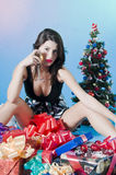Sexy Christmas. A sexy woman with a glass of wine sitting in presents near a Christmas tree Royalty Free Stock Image