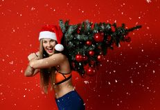 Christmas fitness sport woman wearing santa hat holding xmas tree on her shoulders. Running forward on a red background stock photo