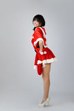 Sexy Christmas girl. Of Asian standing and smiling against gray background in studio Royalty Free Stock Photography