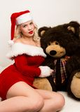 christmas girl embraces with a big teddy bear. blonde woman dressed as Santa stock images