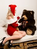 christmas girl embraces with a big teddy bear. blonde woman dressed as Santa stock photography