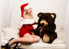 christmas girl embraces with a big teddy bear. blonde woman dressed as Santa stock photos