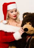 christmas girl embraces with a big teddy bear. blonde woman dressed as Santa royalty free stock image