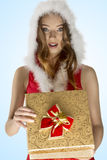 Sexy christmas girl opening gift box. Portrait very sexy christmas woman with red dress and fur hood opening pretty gift box and looking in camera with happy Royalty Free Stock Image