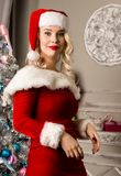 Sexy christmas girl posing. blonde woman dressed as Santa in front of camera Stock Image