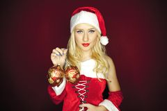 Sexy Christmas girl with tree ornaments on red background Royalty Free Stock Photos
