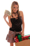 Sexy Christmas Shopper. Beautiful and sexy fashion model Christmas shopping with a bag of gifts in one hand and a fan of cash in the other Royalty Free Stock Images