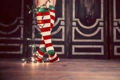 Sexy Christmas Socks. A woman legs wearing sexy christmas socks with christmas lights Stock Photo