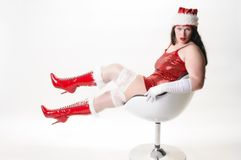 Sexy christmas woman in armchair. Overweight woman with long dark hair wearing a short red sequined dress and fits lasciviously a chair so that you can see her Stock Photos