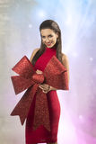 Sexy christmas woman. Sexy brunette woman in christmas portrait posing with red dress and big red bow, smiling and looking in camera Royalty Free Stock Image