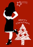 Sexy christmas woman on red background. Sexy christmas woman wishing Merry Christmas, white christmas tree on a red background Royalty Free Stock Images