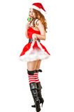 Sexy christmas woman wearing santa claus clothes. Sexy christmas young adult woman wearing santa claus clothes and holding lollipop isolated on white background Royalty Free Stock Images