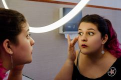 Chubby woman putting on some makeup. Chubby woman putting on makeup, makeup in front of the mirror royalty free stock photos