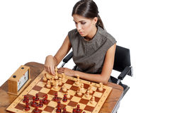 Sexy cleaver brunette woman playing chess Stock Photography