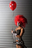Sexy clown wearing a spike bra while holding a red balloon Royalty Free Stock Images