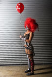 Sexy clown wearing a spike bra while holding a red balloon Royalty Free Stock Photography