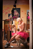And complacent blonde woman in pink skirt and corset. Cute, and complacent blonde woman in pink skirt and corset stock image