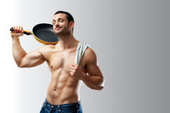 Sexy Cook Teasing. A handsome muscular cook posing with a pan on his shoulder on a neutral background with space for text Stock Image
