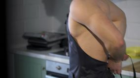 Sexy cook wearing an apron. Man sports, strong, athletic, sexy. Having dressed an apron on a naked body stock video footage