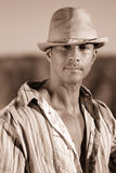 Sexy country boy. Portrait of a sexy country boy, wearing a striped shirt and hat. Sepia toned Royalty Free Stock Images