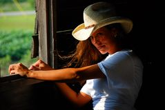 Sexy country girl. Sexy girl with long hair and cowboy hat looks into the camrea with sunset light coming through wooden window frame of a barn. tiny highlights Stock Photos