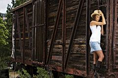 Sexy Country Girl on a train. A sexy country girl with a cowboy hat and boots hanging onto a train car Royalty Free Stock Photos