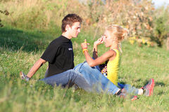 Couple boy and girl. Young couple enjoying each other on the grass in the park stock photo