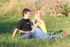 Couple boy and girl. Young couple enjoying each other on the grass in the park royalty free stock images