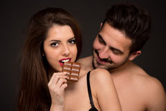 Sexy couple with chocolate in studio Stock Images