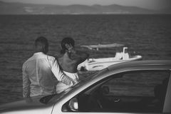 couple. Couple in love stand near silver car, sea on background. Couple arrived on vacation, honeymoon. Man and stock photo