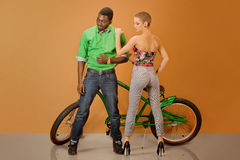 Sexy couple in front of a bycicle on orange background Stock Images