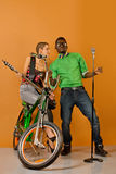 Sexy couple in front of a bycicle on orange background Royalty Free Stock Image