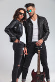 Couple in leather jackets holding electric guitar. On grey studio background Royalty Free Stock Photo