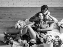 Couple lovers on floor. Couple young beautiful cute lovers in love pretty girl and sexi men with boxes of flowers hug on wooden floor stock images