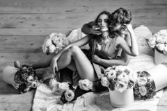 Couple lovers on floor. Couple young beautiful cute lovers in love pretty girl and sexi men with boxes of flowers hug on wooden floor stock photos