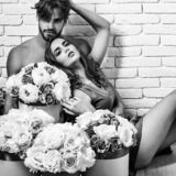 Couple lovers on floor. Couple young beautiful cute lovers in love pretty girl and sexi men with boxes of flowers hug on floor on white brick wall royalty free stock photo