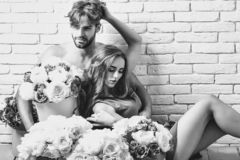 Couple lovers on floor. Couple young beautiful cute lovers in love pretty girl and sexi men with boxes of flowers hug on floor on white brick wall stock photos