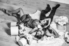 Couple lovers on floor. Couple young beautiful cute lovers in love pretty girl and sexi men lying on back on white bedsheet among flowers on wooden floor stock image