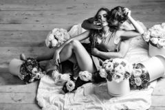 Couple lovers on floor. Couple young beautiful cute lovers in love pretty girl and sexi men with boxes of flowers hug on wooden floor royalty free stock photos