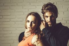 Couple of lovers. Couple young beautiful cute lovers in love pretty girl in orange dress has long hair and handsome men on white brick wall background royalty free stock photos