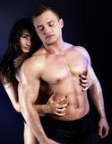 Sexy couple posing. Sexy couple posing in  studio. Handsome muscular men with girlfriend Stock Photos