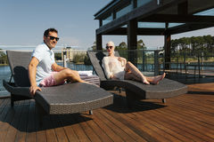 Couple on sunbed. Sexy couple relaxing on sunbeds Royalty Free Stock Photo