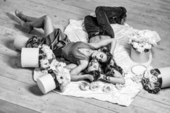 Couple lovers on floor. Couple young beautiful cute lovers in love pretty girl and sexi men lying on back on white bedsheet among flowers on wooden floor royalty free stock image