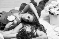 Couple lovers on floor. Couple young beautiful cute lovers in love pretty girl and sexi men lying on back on white bedsheet among flowers on wooden floor royalty free stock photography