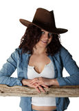 Sexy Cowgirl. Leaning on a cedar rail Royalty Free Stock Photography