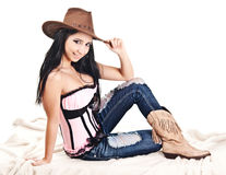 Sexy Cowgirl. Pretty cowgirl sitting on a fur rug wearing a corset and hat Royalty Free Stock Image