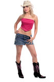 Cowgirl. Beautiful young cowgirl with blond hair in a short denim skirt, pink top, pink and brown suede boots and a cowboy hat royalty free stock photos
